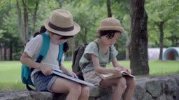 앉아서 책을 보고 있는 여자아이와 남자아이의 모습