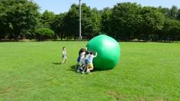 다섯명의 아이들이 큰 공을 굴리고 가는 모습