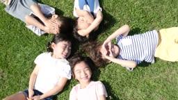 잔디밭에 누워서 환하게 웃고 있는 다섯명의 아이들