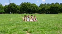 잔디밭에 앉아서 손을 흔들고 있는 아이들의 모습