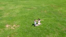 카메라를 향해 손을 흔드는 남자아이와 여자아이의 모습