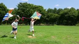 연을 날리면서 뛰어가는 남자아이와 여자아이의 모습