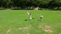 연을 날리면서 뛰는 남자아이와 여자아이의 모습