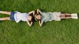 잔디밭에 누워있는 남자아이와 여자아이의 모습