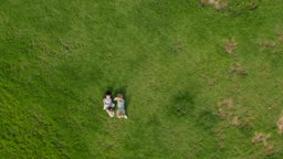잔디밭에 누워서 장난치는 남자아이와 여자아이의 모습