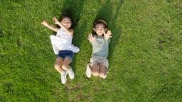 잔디밭에 누워서 하늘 향해 손을 흔드는 남자아이와 여자아이의 모습