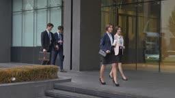 건물 밖을 회사원들이 지나가는 모습