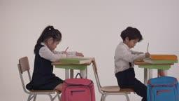 책상에 앉아서 공부를 하는 한국 여자 아이와 남자 아이의 모습