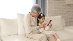 서울시 쇼파에 앉아 핸드폰을 만지는 한국인 할아버지와 손녀의 모습