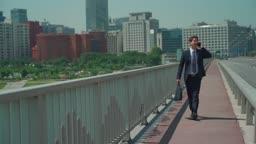 다리 위에서 통화하며 걷는 직장인 남성