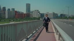 다리 위를 급하게 뛰어가는 직장인 남성
