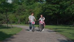 공원에서 자전거를 끌고가는 커플