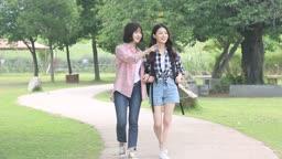 공원에서 이야기 나누며 팔짱끼고 걷는 여자들