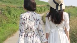 손잡고 길을 걷고 있는 원피스 입은 여자들 뒷모습