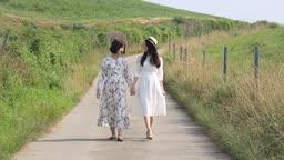 손잡고 길을 걷고 있는 원피스 입은 여자들