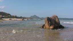 Blick auf einen Strand mit Felsen bei Sonnenschein.