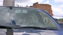 teenager on car looks at itself in mirror.