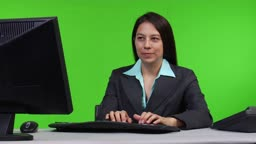 Junge Geschaeftsfrau arbeitet am PC - zoom out - Green Screen Version --- Young business woman typing on PC - green screen version
