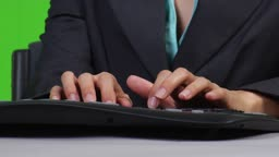Junge Geschaeftsfrau arbeitet am PC - zoom out - Green Screen Version --- Young business woman typing on PC - zoom out - green screen version
