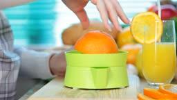 female hand squeezes orange juice on a juicer