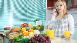 Pregnant woman talking on her mobile phone and drink orange juice in the kitchen
