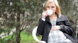 Pregnant woman drinking tea outdoors