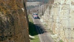 railway train runs under the road bridge  in the gorge