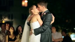 newlyweds kissing at night, surrounded by visitors and relatives