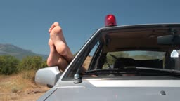 Woman hanging out legs from  police car