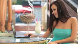 Beautiful Young woman Using Laptop at Outdoor Cafe