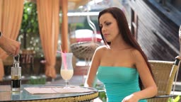 attractive young woman in a cocktail dress having dinner in a restaurant. Waiter setting the table