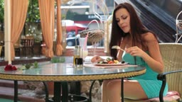 attractive young woman in a cocktail dress having dinner in a restaurant. Greek salad