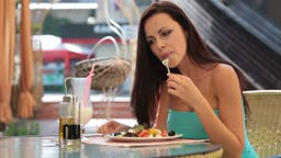 young woman having dinner at a restaurant. Her choice Greek salad and a cocktail