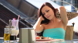Young Woman eating lunch at a relaxed outdoor restaurant