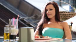 young brunette woman relaxing after dinner in a restaurant