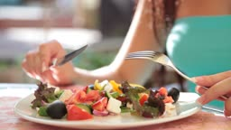 unrecognizable young woman has dinner in restaurant, Greek salad