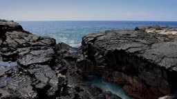 Ocean water splashes out from under a natural arch formed from volcanic rock in Hawaii. A Kayaker rows by in the background