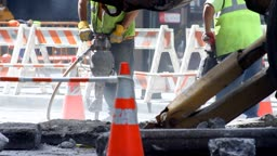 Two construction workers operating jackhammers on a city street