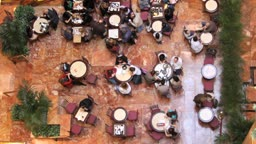 A time lapse shot and a real time shot, of a busy indoor cafe from a high angle