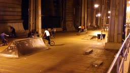 Youth riding bikes in an urban skatepark in New York at night