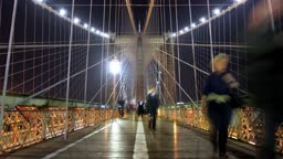 Low angle view on the walkway of Brooklyn Bridge at night. Time lapse with motion blur.