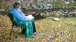 Elderly woman reading a book outdoors Side View