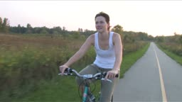 Moving alongside a young woman riding a bike on a paved prairie path with the sunset behind her.