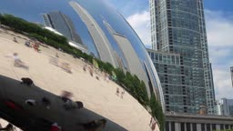 Time lapse of tourists exploring Millennium Park in the reflection of the Cloud Gate sculpture, with the Chicago skyline.