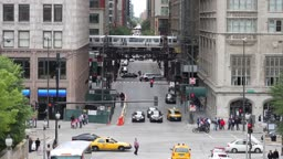 High angle of a Michigan Avenue intersection and the border of The Loop in Chicago, with traffic, pedestrians, and en el train passing by.