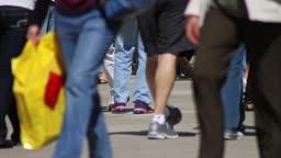The feet of dozens of pedestrians walking on the sidewalk in Chicago