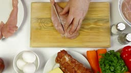 Female Hands cutting chicken breast