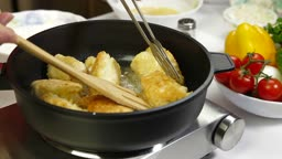 Female frying chicken breast roll on a pan.