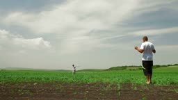Young Family Playing With Kite In Field