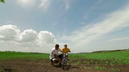 Happy Family Riding Bicycle. Father Helping Child Learn To Ride A Bike